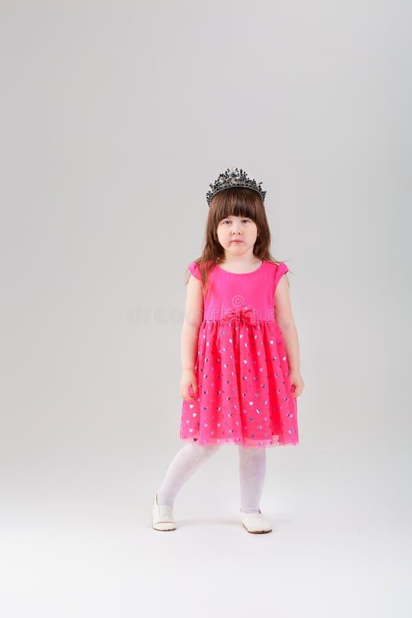 Όμορφο μικρό κορίτσι στο ρόδινο φόρεμα πριγκηπισσών με την κορώνα σε γκρίζο στοκ εικόνες