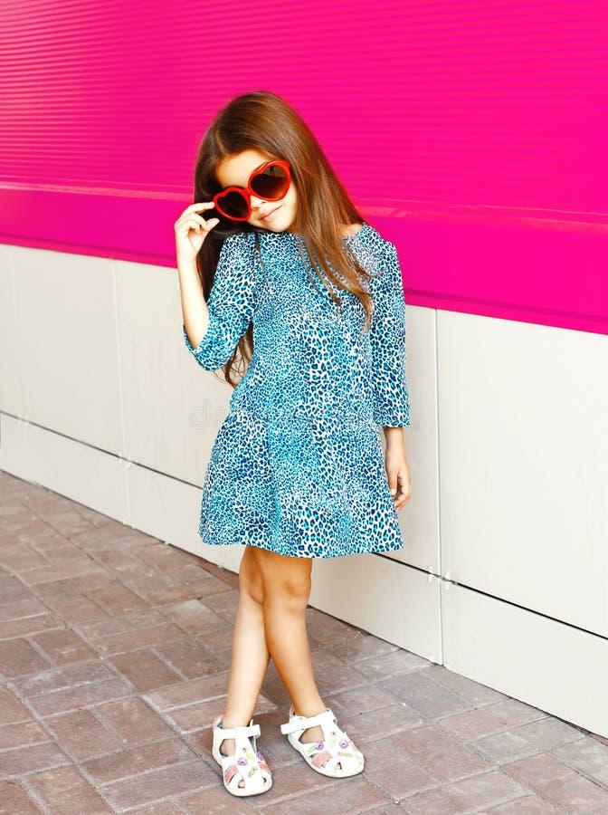 Όμορφο μικρό κορίτσι στο φόρεμα τυπωμένων υλών λεοπαρδάλεων στο ζωηρόχρωμο ροζ στοκ φωτογραφία
