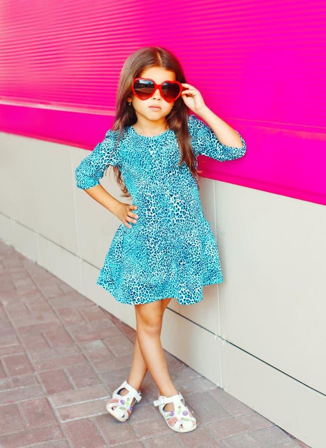 Όμορφο μικρό κορίτσι στο φόρεμα τυπωμένων υλών λεοπαρδάλεων στο ζωηρόχρωμο ροζ στοκ εικόνες