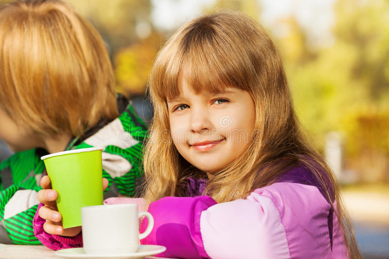Όμορφο μικρό ξανθό κορίτσι με το πράσινο φλυτζάνι στοκ εικόνα