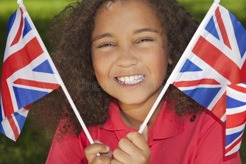 Όμορφο μικτό κορίτσι φυλών με τις σημαίες του Union Jack στοκ φωτογραφία