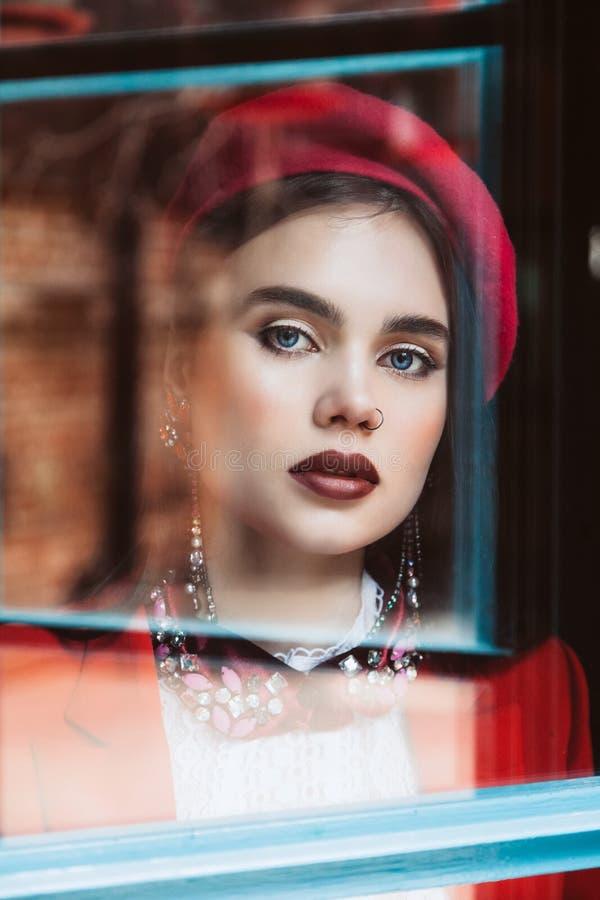 Όμορφο μοντέλο μελαχρινής μελαχρινής με μπλε μάτια σε κόκκινο μπερέ κοιτάζει μέσα από το γυαλί στην κάμερα Ρετούς δέρματος στοκ φωτογραφίες