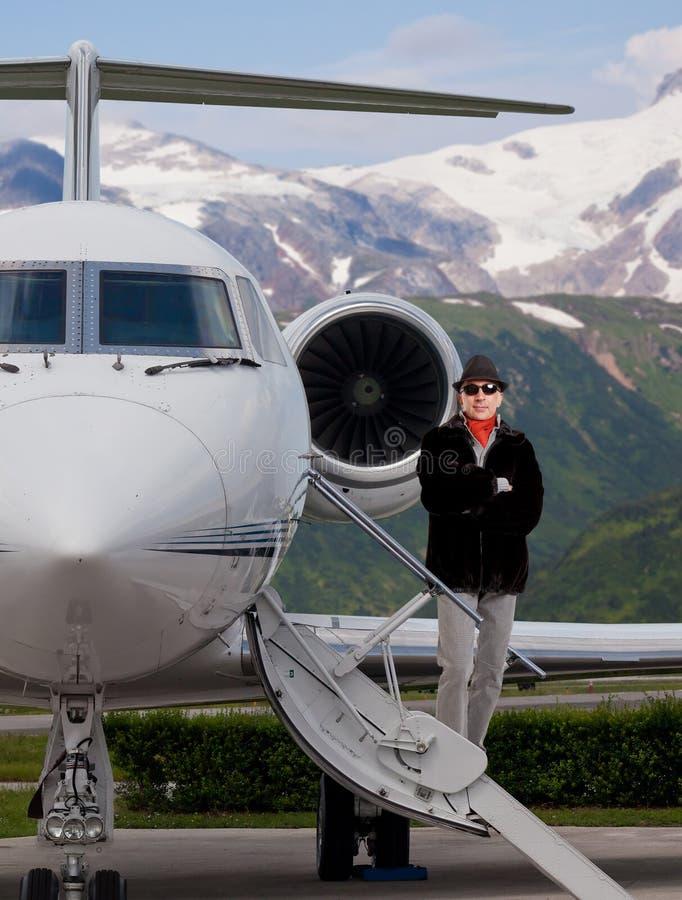 Όμορφο μοντέρνο άτομο στα βήματα ενός ιδιωτικού αεριωθούμενου αεροπλάνου στοκ φωτογραφία