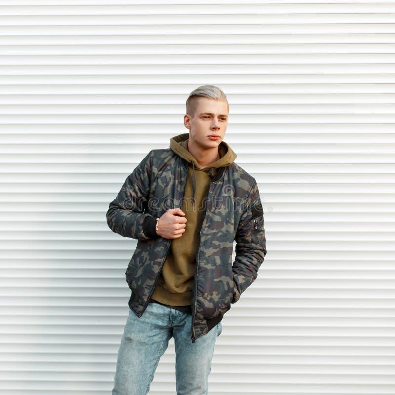 Όμορφο μοντέρνο άτομο στο καθιερώνον τη μόδα στρατιωτικό σακάκι με το hoodie στοκ φωτογραφία με δικαίωμα ελεύθερης χρήσης