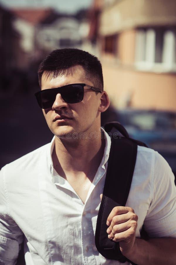 Όμορφο μοντέρνο καυκάσιο άτομο που φορά τα καθιερώνοντα τη μόδα γυαλιά ηλίου που θέτουν στο κλίμα οδών με το σακίδιο πλάτης στους στοκ εικόνα με δικαίωμα ελεύθερης χρήσης