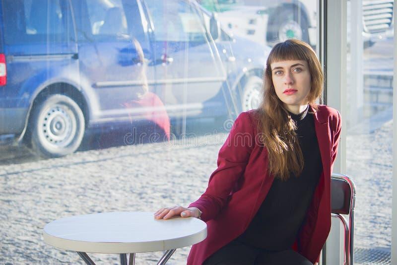 Όμορφο μοντέρνο κορίτσι σε έναν πίνακα σε έναν καφέ στοκ φωτογραφίες