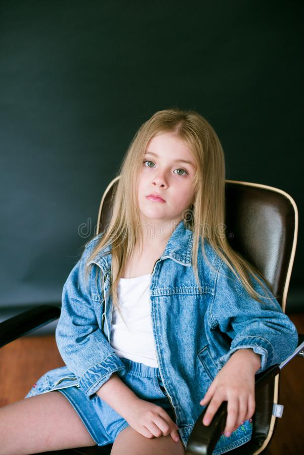 Όμορφο μοντέρνο μικρό κορίτσι με τα ξανθά μαλλιά στα ενδύματα τζιν σε ένα μαύρο υπόβαθρο στοκ φωτογραφίες