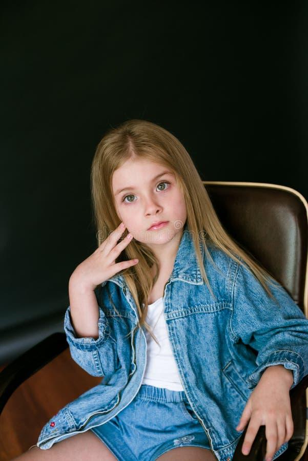 Όμορφο μοντέρνο μικρό κορίτσι με τα ξανθά μαλλιά στα ενδύματα τζιν σε ένα μαύρο υπόβαθρο στοκ εικόνες