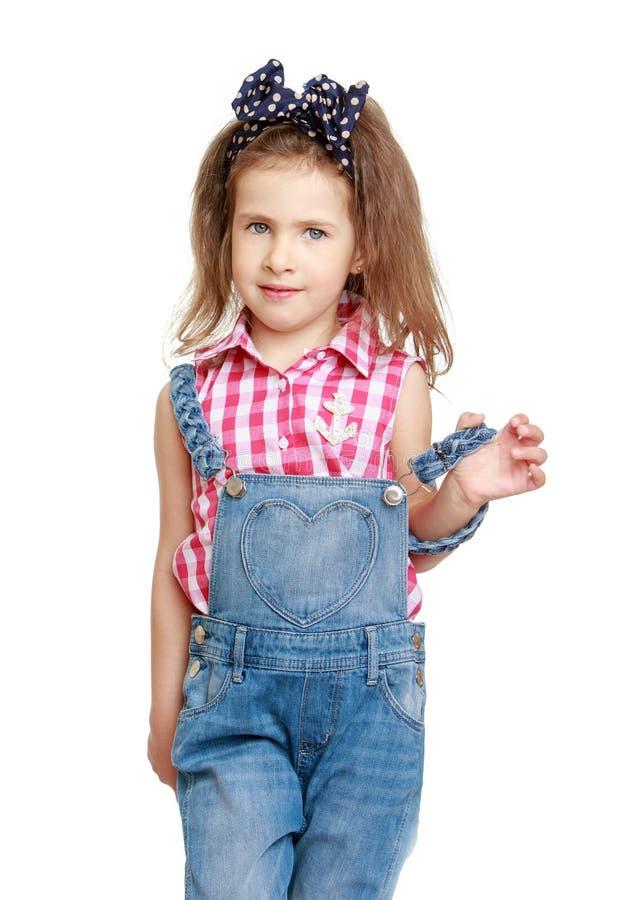 Όμορφο, μοντέρνο μικρό κορίτσι στις φόρμες τζιν στοκ εικόνες