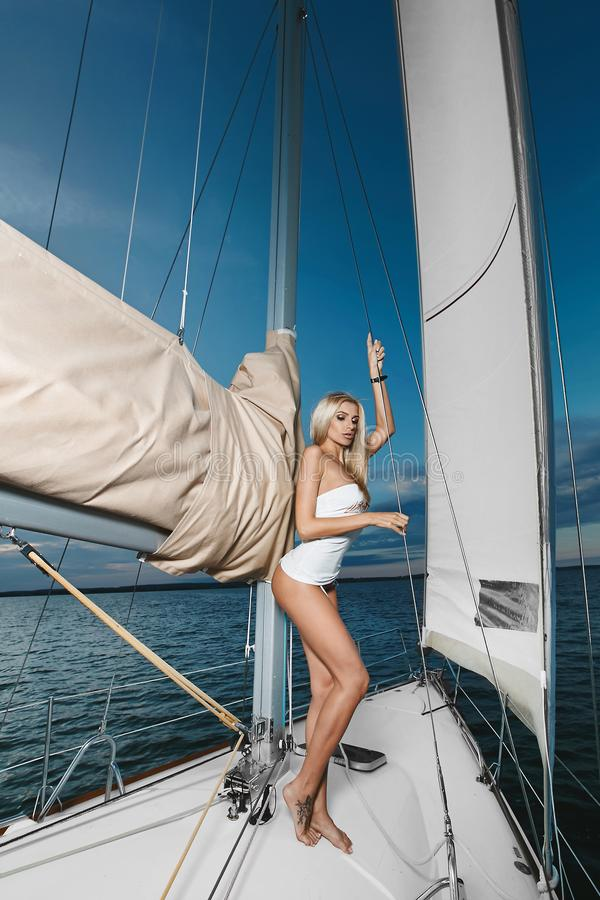 Όμορφο μοντέρνο ξανθό κορίτσι στην τοποθέτηση μπικινιών και μπλουζών σε ένα σκάφος γιοτ στοκ φωτογραφία