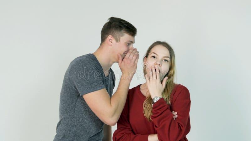 Όμορφο μυστικό ψιθυρίσματος κοριτσιών στο αυτί του γελώντας φίλου της στο άσπρο υπόβαθρο - έννοια φιλίας στοκ φωτογραφίες με δικαίωμα ελεύθερης χρήσης