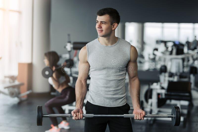 Όμορφο μυϊκό άτομο που επιλύει με τους αλτήρες στη γυμναστική στοκ εικόνες