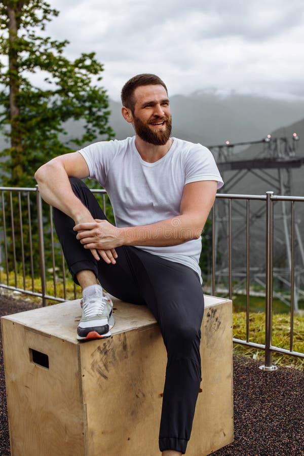 Όμορφο μυϊκό άτομο hunk που εξετάζει τα βουνά από την αιχμή στοκ φωτογραφίες