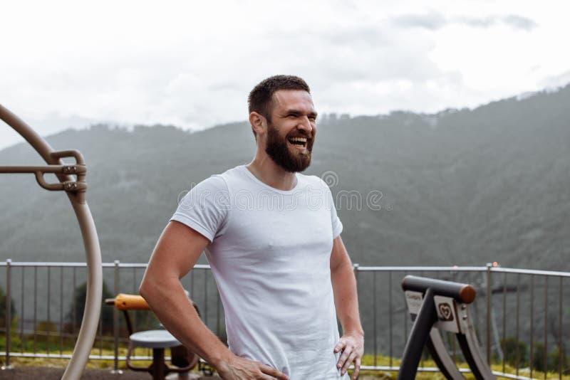 Όμορφο μυϊκό άτομο hunk που εξετάζει τα βουνά από την αιχμή στοκ εικόνα