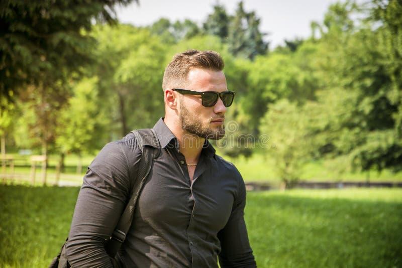 Όμορφο μυϊκό άτομο Hunk υπαίθριο στο πάρκο πόλεων στοκ εικόνα