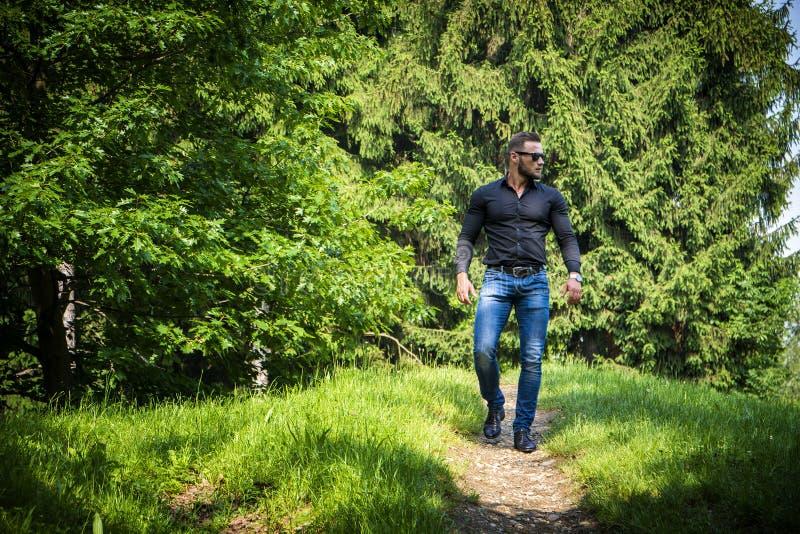 Όμορφο μυϊκό άτομο Hunk υπαίθριο στο πάρκο πόλεων στοκ εικόνες