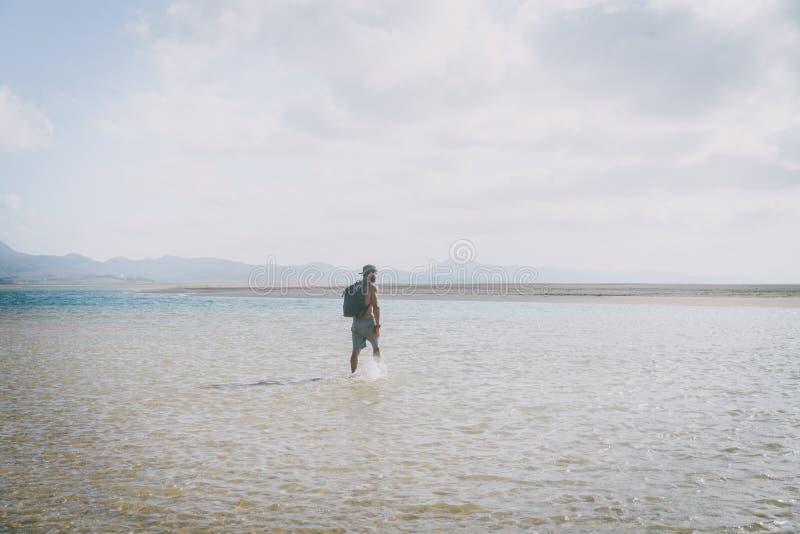 Όμορφο μυϊκό γενειοφόρο άτομο που περπατά στην ακροθαλασσιά στην ανατολή με το σακίδιο πλάτης στοκ φωτογραφία με δικαίωμα ελεύθερης χρήσης
