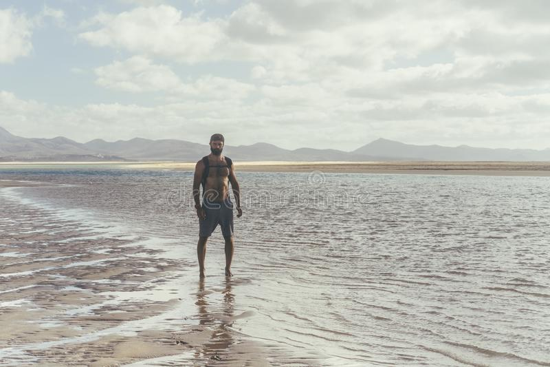 Όμορφο μυϊκό γενειοφόρο άτομο που στέκεται στην ακροθαλασσιά στην ανατολή Δευτερεύον πορτρέτο του υγιούς νέου γενειοφόρου τρεξίμα στοκ φωτογραφίες με δικαίωμα ελεύθερης χρήσης