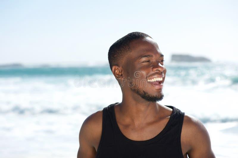 Όμορφο νέο άτομο αφροαμερικάνων που γελά στην παραλία στοκ εικόνα με δικαίωμα ελεύθερης χρήσης