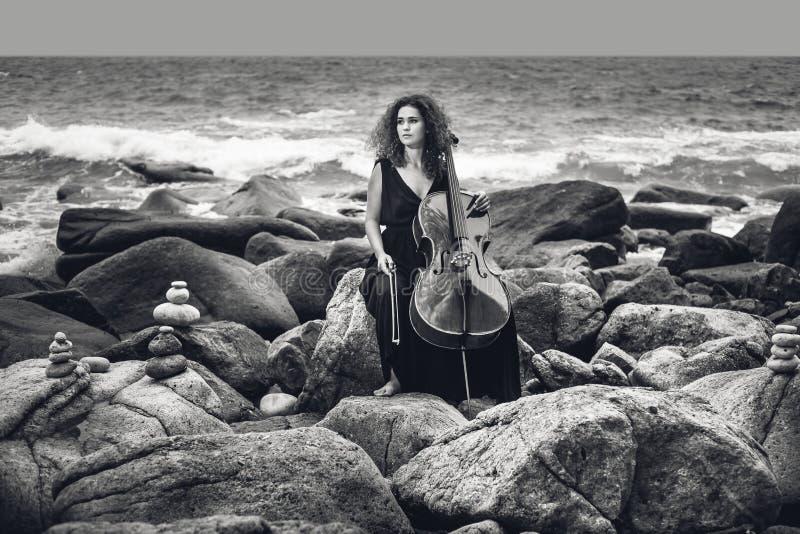 Όμορφο νέο βιολοντσέλο παιχνιδιού γυναικών στην παραλία πετρών στο θυελλώδες wea στοκ φωτογραφίες