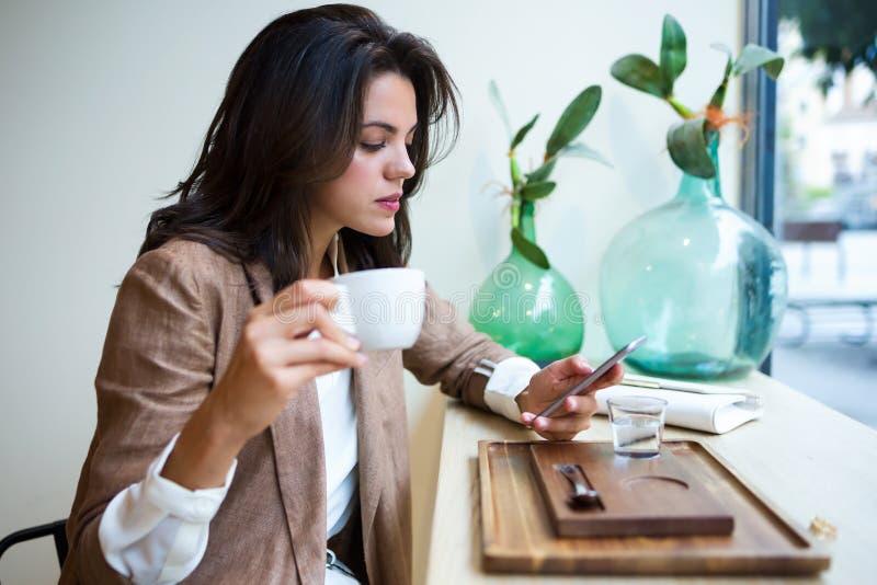 Όμορφο νέο επιχειρηματιών με το κινητό τηλέφωνό της στη καφετερία στοκ εικόνα