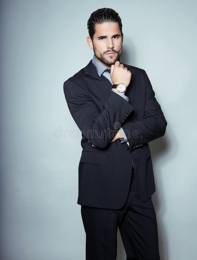 Όμορφο νέο επιχειρησιακό άτομο στο κοστούμι στο γκρίζο υπόβαθρο στοκ εικόνες