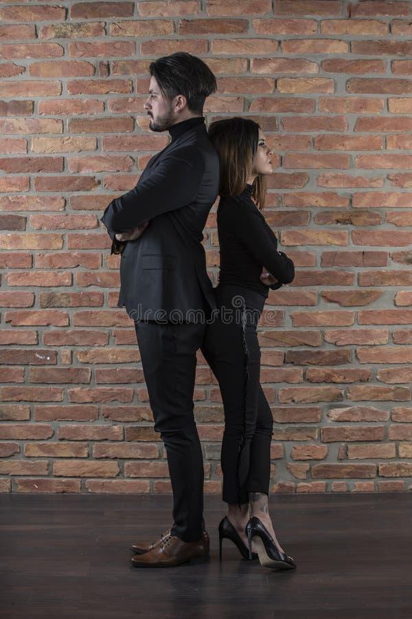 Όμορφο νέο επιχειρησιακό ζεύγος που στέκεται πλάτη με πλάτη μπροστά από έναν τουβλότοιχο στοκ φωτογραφία με δικαίωμα ελεύθερης χρήσης