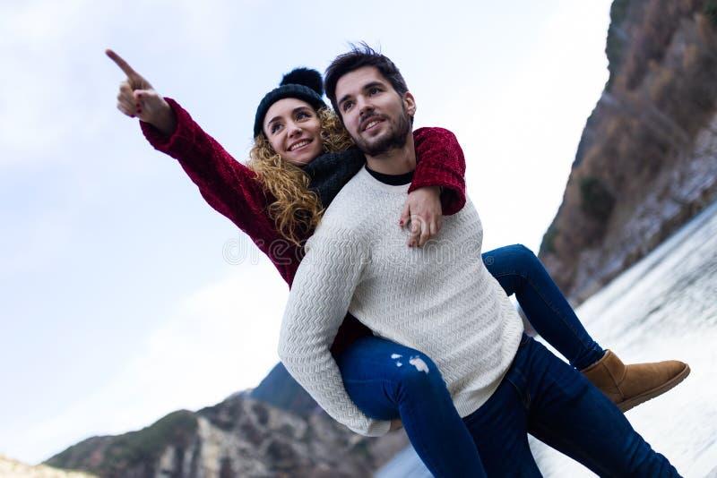 Όμορφο νέο ζεύγος ερωτευμένο πέρα από το χειμερινό υπόβαθρο στοκ φωτογραφία με δικαίωμα ελεύθερης χρήσης