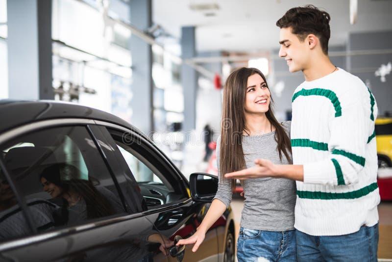 Όμορφο νέο ζεύγος που στέκεται στον αντιπρόσωπο που επιλέγει το αυτοκίνητο που αγοράζει Άτομο που δείχνεται στο αυτοκίνητο στοκ εικόνες