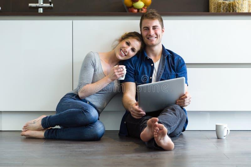 Όμορφο νέο ζεύγος που χρησιμοποιεί αυτοί ψηφιακή ταμπλέτα στην κουζίνα στοκ φωτογραφία με δικαίωμα ελεύθερης χρήσης