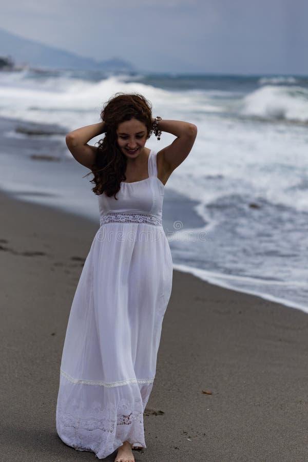 Όμορφο νέο θηλυκό που περπατά από την παραλία κατά τη διάρκεια της θύελλας στοκ εικόνα