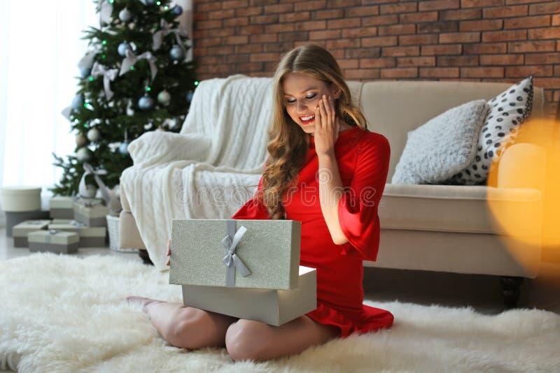 Όμορφο νέο κιβώτιο δώρων ανοίγματος γυναικών στο σπίτι στοκ εικόνες
