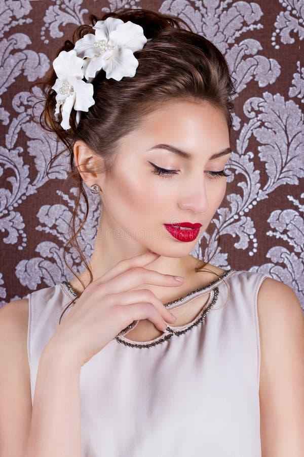 Όμορφο νέο κομψό κορίτσι με το φωτεινό makeup με τα κόκκινα χείλια με έναν όμορφο γάμο hairstyle για τη νύφη με τα άσπρα λουλούδι στοκ φωτογραφίες