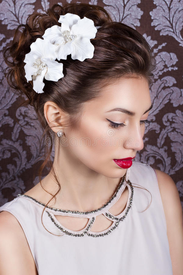 Όμορφο νέο κομψό κορίτσι με το φωτεινό makeup με τα κόκκινα χείλια με έναν όμορφο γάμο hairstyle για τη νύφη με τα άσπρα λουλούδι στοκ εικόνες