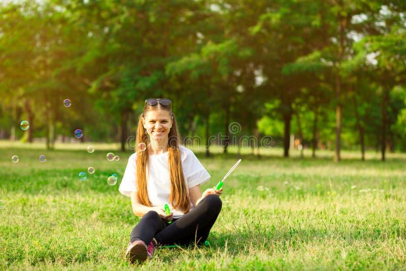 Όμορφο νέο κορίτσι γυναικών με τα μπαλόνια φυσαλίδων παιχνιδιού στις διακοπές κήπων στοκ εικόνες με δικαίωμα ελεύθερης χρήσης