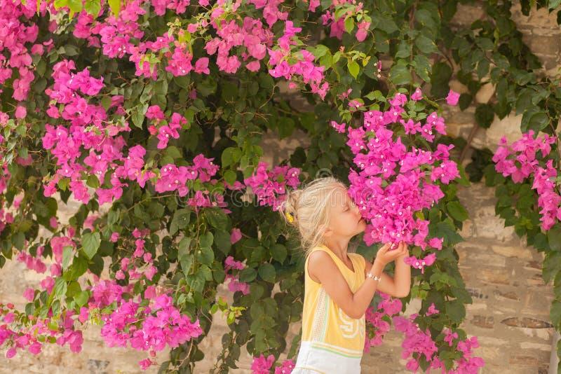 Όμορφο νέο κορίτσι κοντά στα λουλούδια στοκ εικόνες