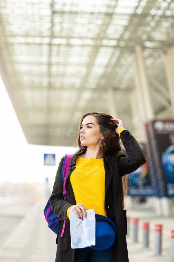 Όμορφο νέο κορίτσι με ένα σακίδιο πλάτης πίσω από τον ώμο της που κρατά έναν χάρτη, στην οδό κοντά στον αερολιμένα στοκ φωτογραφίες