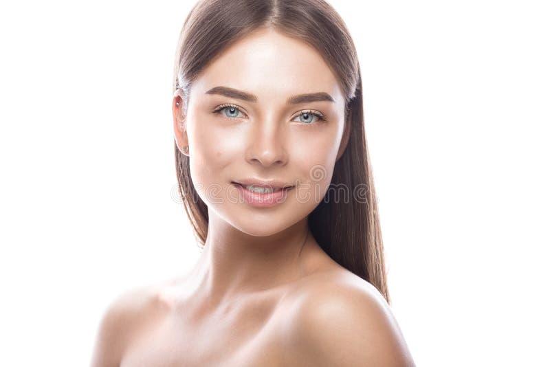 Όμορφο νέο κορίτσι με μια ελαφριά φυσική σύνθεση και ένα τέλειο δέρμα Πρόσωπο ομορφιάς στοκ εικόνες