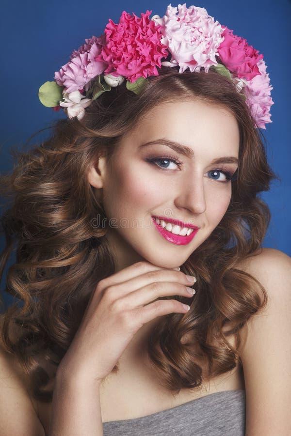 Όμορφο νέο κορίτσι με μια floral διακόσμηση στην τρίχα της σε ένα μπλε υπόβαθρο στεφάνι γυναικών λουλο&up Πρόσωπο ομορφιάς Μόδα p στοκ φωτογραφία