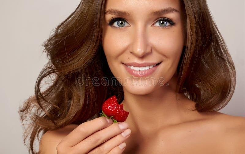 Όμορφο νέο κορίτσι με τα ευθέα άσπρα δόντια που χαμογελούν και που τρώνε τις φράουλες στοκ φωτογραφίες