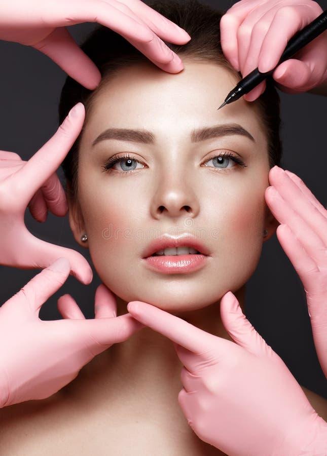 Όμορφο νέο κορίτσι με τη φυσική nude σύνθεση με τα καλλυντικά εργαλεία στα χέρια Πρόσωπο ομορφιάς στοκ εικόνες
