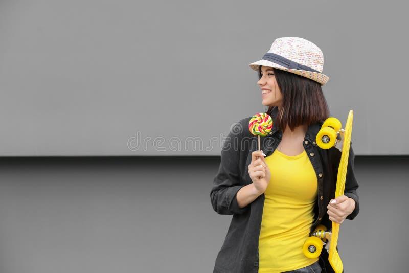 Όμορφο νέο κορίτσι με το lollipop και skateboard στο γκρίζο υπόβαθρο στοκ εικόνα με δικαίωμα ελεύθερης χρήσης