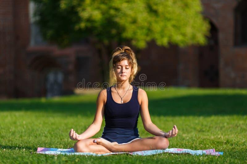 Όμορφο νέο κορίτσι που κάνει τις ασκήσεις γιόγκας στοκ εικόνα με δικαίωμα ελεύθερης χρήσης