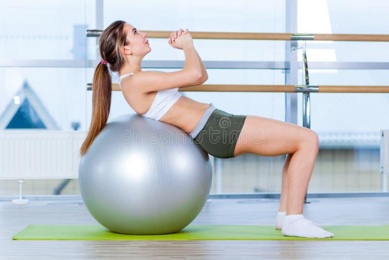 Όμορφο νέο κορίτσι που κάνει τις ασκήσεις με την κατάλληλη σφαίρα στη γυμναστική στοκ φωτογραφία