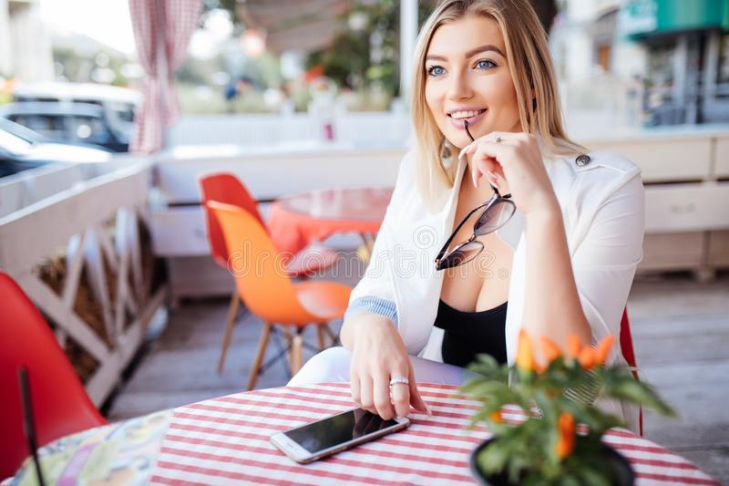 Όμορφο νέο κορίτσι που στηρίζεται σε έναν καφέ ελκυστική ξανθή πρότυπη συνεδρίαση με ένα φλιτζάνι του καφέ σε έναν υπαίθριο καφέ  στοκ φωτογραφία με δικαίωμα ελεύθερης χρήσης