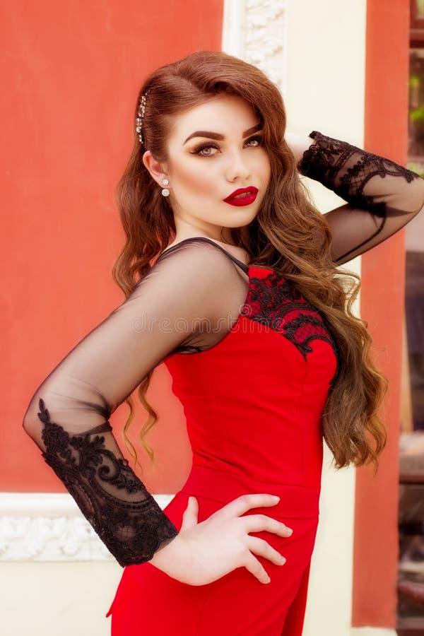 Όμορφο νέο κορίτσι σε ένα κόκκινο μακρύ φόρεμα βραδιού στοκ φωτογραφίες
