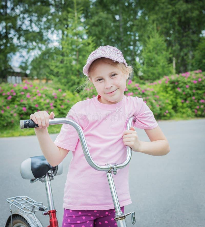 Όμορφο νέο κορίτσι σε ένα ποδήλατο στοκ εικόνες