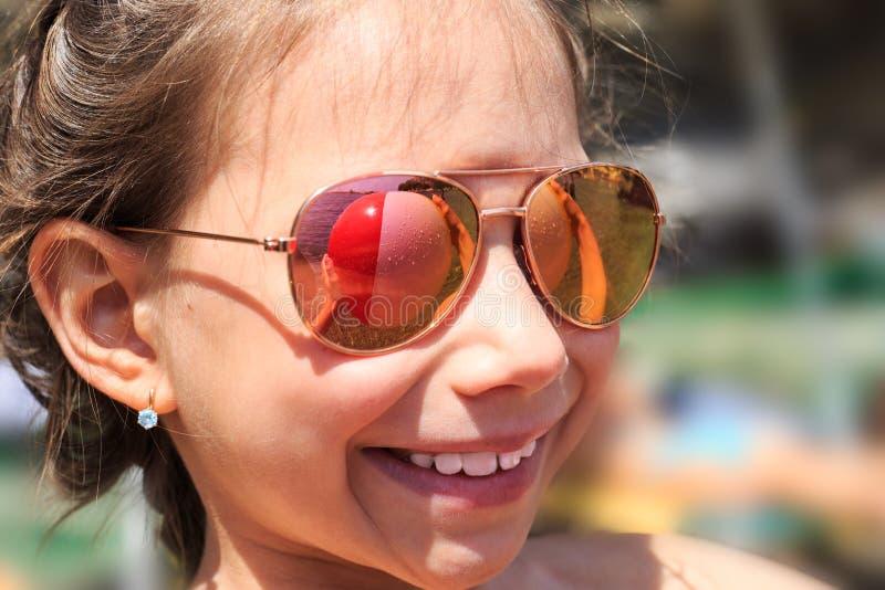 Όμορφο νέο κορίτσι στα γυαλιά ηλίου με το rerlection σφαιρών παραλιών στοκ εικόνες