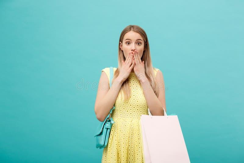 Όμορφο νέο κορίτσι στα κίτρινα χέρια εκμετάλλευσης φορεμάτων με συγκλονισμένη την πρόσωπο έκφραση του προσώπου της στοκ εικόνες