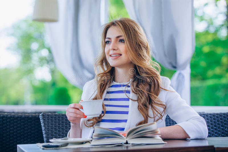 Όμορφο νέο κορίτσι στον υπαίθριο καφέ που διαβάζει το α στοκ εικόνες